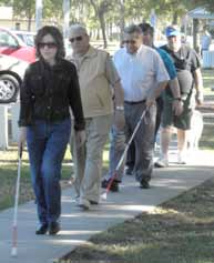 Pat Lopez leads a group of walkers all holding long white canes