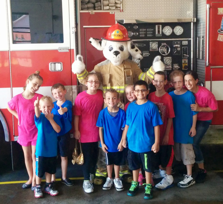 The children at the fire hall, standing with the fire station mascot in front of the fire truck.